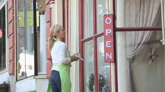 stockvideo's en b-roll-footage met ms pan woman hanging 'open' sign outside shop door, cleaning window, petersburg, virginia, usa - bord open