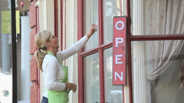 stockvideo's en b-roll-footage met ms pan woman hanging 'open' sign outside shop door, cleaning window, petersburg, virginia, usa - etalage