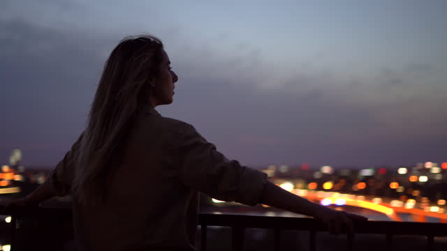 vídeos de stock e filmes b-roll de woman hanging out on rooftop - retroiluminado