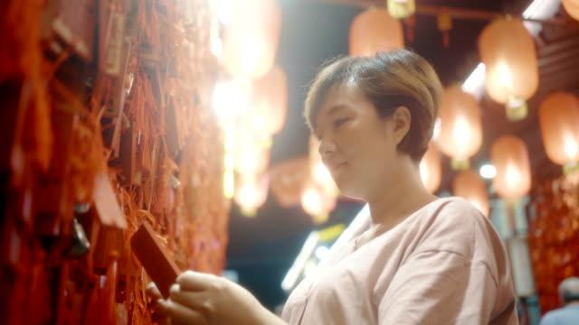 stockvideo's en b-roll-footage met het hangende gebedsoffers van de vrouw voor goed geluk - zijde