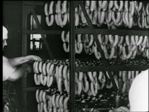 b/w 1922 woman hanging sausage links on rack in factory / chicago / newsreel - sausage stock videos & royalty-free footage