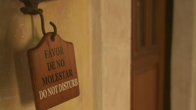 stockvideo's en b-roll-footage met cu woman hanging sign reading 'favor de no molestar - do not disturb' outside hotel room door / merida, mexico  - alleen één mid volwassen vrouw