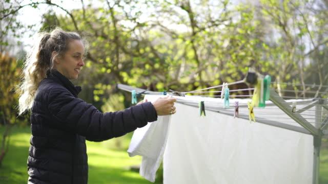 frau hängt wäsche auf, um im garten zu trocknen - hängen stock-videos und b-roll-filmmaterial