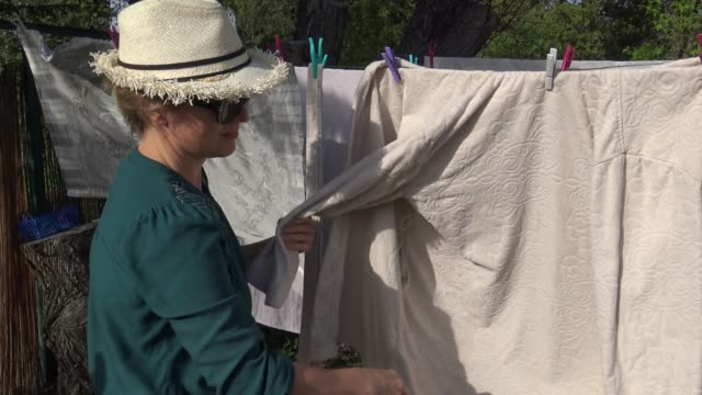 woman hanging up wet laundry on clothesline to dry in the back yard - hanging stock videos & royalty-free footage
