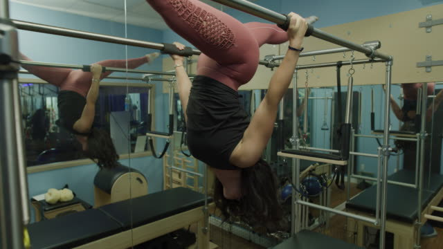 woman hanging upside-down with legs apart on pilates reformer exercise machine / lehi, utah, united states - lehi stock videos & royalty-free footage