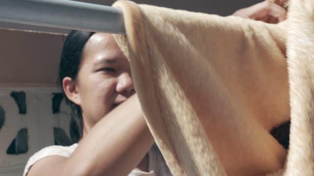 stockvideo's en b-roll-footage met vrouw opknoping natte deken op hanger - wasknijper