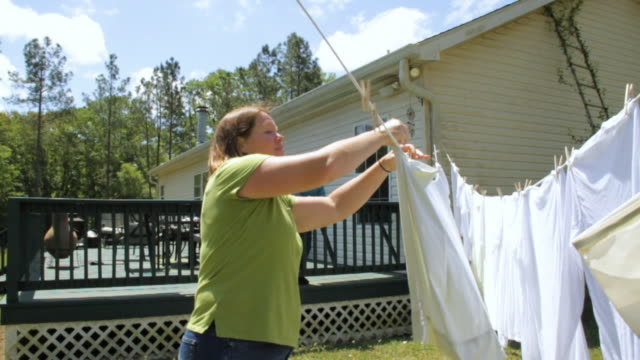 SLO MO MS Woman hanging white clothes on clothesline in front of house / Madison, Florida, USA