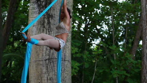 ms ts woman hangs from fabric and spinning around in circles while hanging from large trees in tropical paradise / montezuma, puntarenas, costa rica - kelly mason videos stock videos & royalty-free footage
