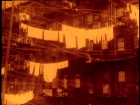a woman hangs laundry on a clothesline from a fire escape on a tenement building - fire escape stock videos and b-roll footage