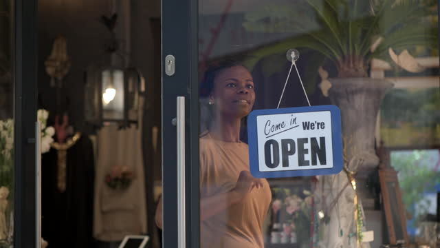 woman hangs open sign on boutique store window - store sign stock videos & royalty-free footage