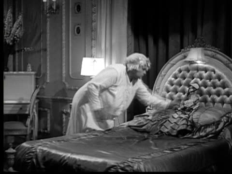 1937 B/W WS Woman (Trixie Friganza) haphazardly throwing pillows off of bed, turning covers back, stretching, and sitting down