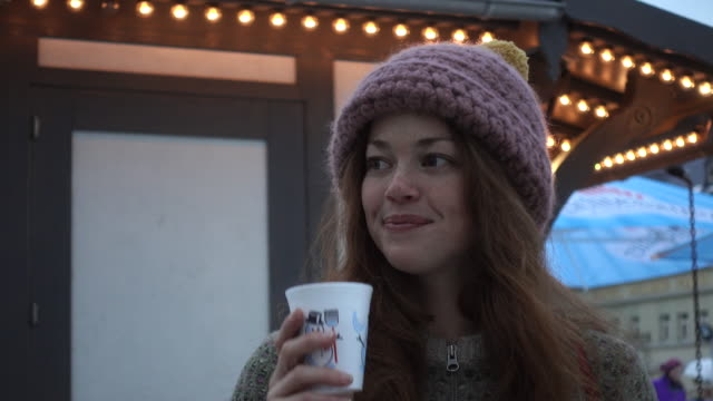 woman happily drinking coffee in front of a food stall - heißes getränk stock-videos und b-roll-filmmaterial