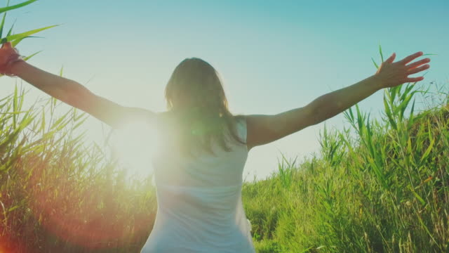 Woman happy and free with outstretched arms to the sun