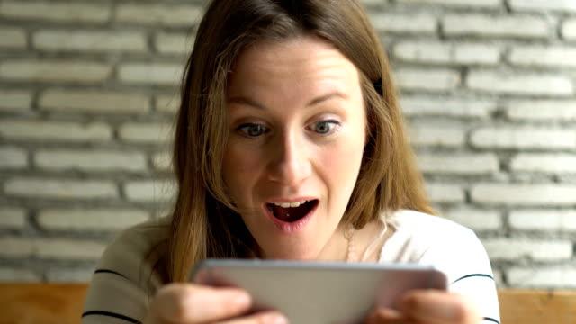 女性の幸せな賭博と彼女の携帯電話で勝利 - 通信点の映像素材/bロール