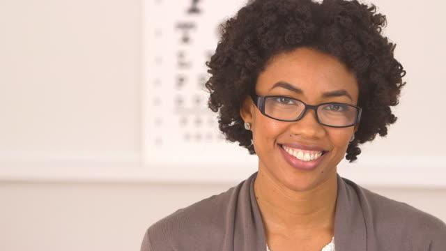 vídeos de stock e filmes b-roll de woman happy with new glasses at eye doctor - só uma mulher de idade mediana