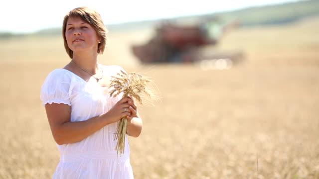 stockvideo's en b-roll-footage met woman harvesting wheat - volkorentarwe