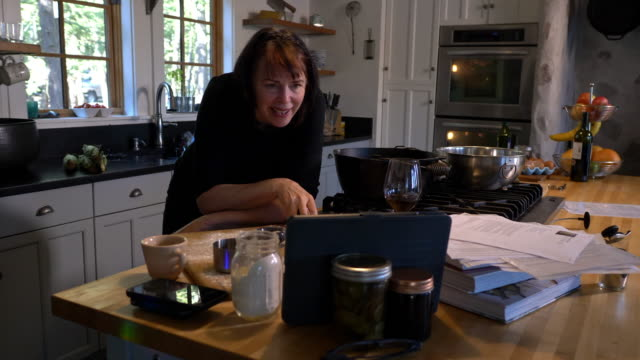 a woman has a video calls with friends / family/ coworkers on her mobile device while cooking in the kitchen. - connection in process stock videos & royalty-free footage