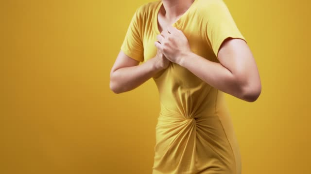 woman has chest pain isolated over yellow background - plain background stock videos & royalty-free footage