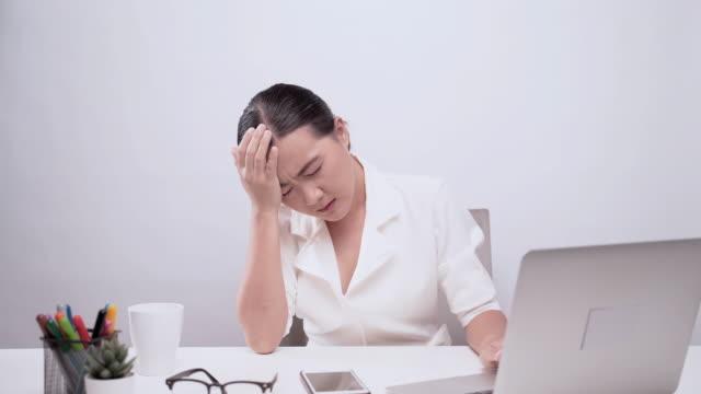 女性は白い背景の上に隔離されたオフィスで頭痛を持っています - 目が回る点の映像素材/bロール