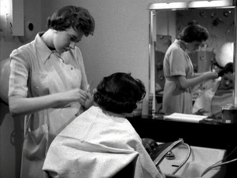 A woman has her hair cut by a hairdresser 1955