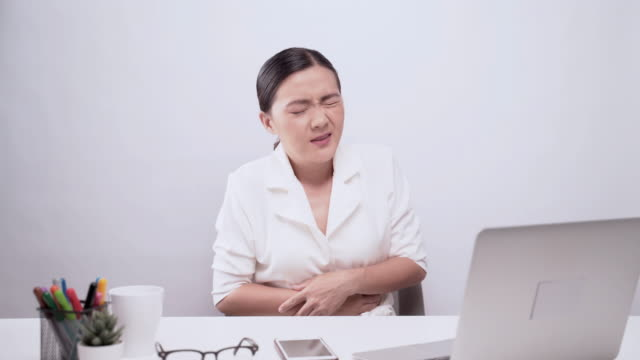 woman has stomachache at office isolated white background - hungry stock videos & royalty-free footage