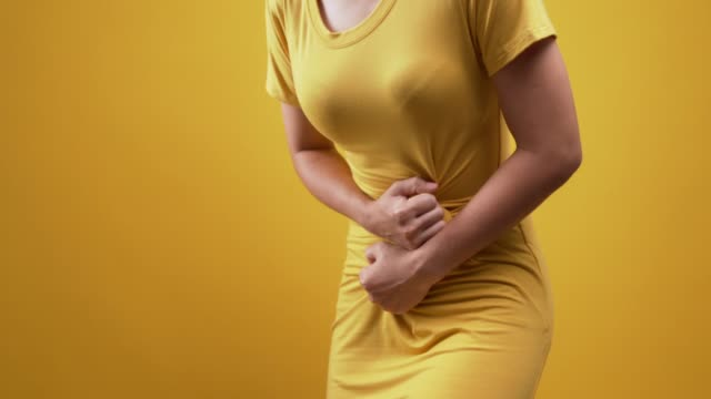 woman has stomachache isolated over yellow background - belly stock videos & royalty-free footage