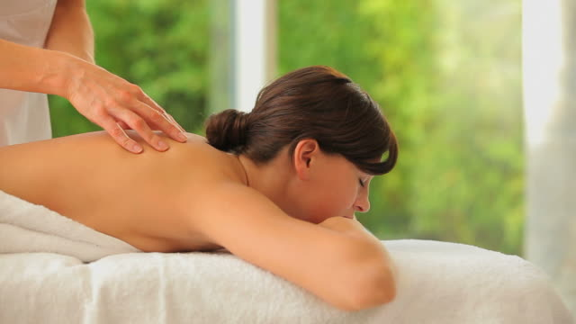 woman having a back massage - massagetisch stock-videos und b-roll-filmmaterial