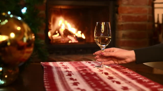 ds woman having a glass of white wine by the fireplace - tablecloth stock videos & royalty-free footage