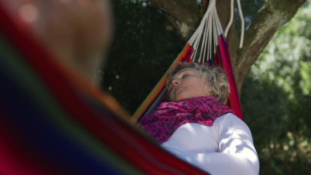 woman having a nap in a hammock. - attività del fine settimana video stock e b–roll