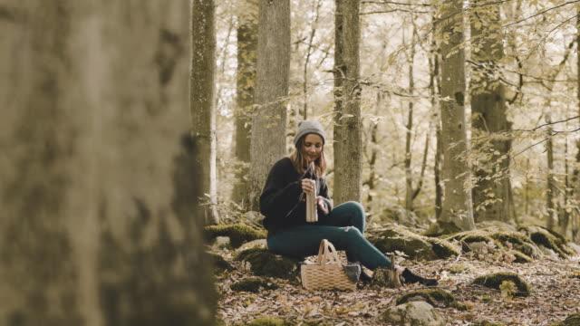 kvinnan har picknick samtidigt plocka svamp i skogen - coffee drink bildbanksvideor och videomaterial från bakom kulisserna