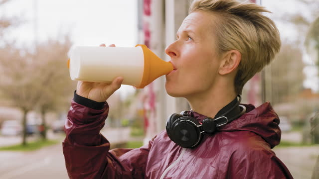woman having a protein drink after her exercise - protein stock videos & royalty-free footage