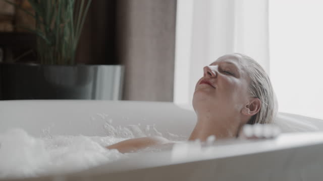 slo mo woman having a relaxing bubble bath in a hot tub - bubble bath stock videos & royalty-free footage