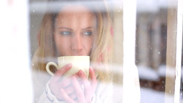 woman having a tea or coffee on snowy day. - toned image stock videos and b-roll footage