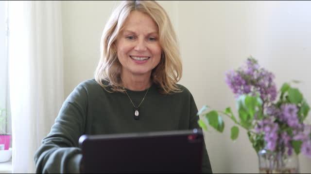 donna che ha una videochiamata sul tablet - cheerful video stock e b–roll
