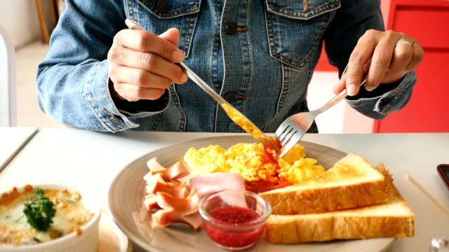 女性の卵パン ホットドッグと朝食 - テーブルマナー点の映像素材/bロール