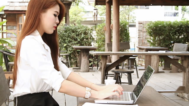 Woman having coffee and using laptop computer