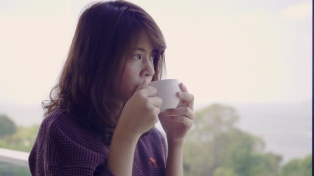 woman having coffee in living room - cup stock videos & royalty-free footage