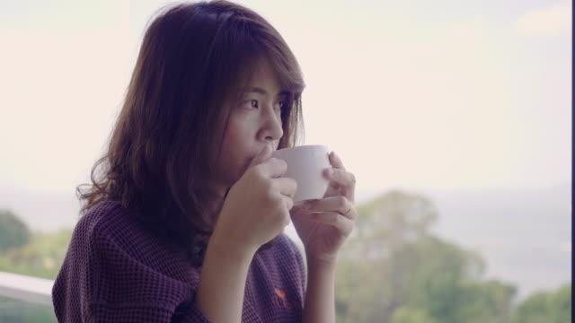 リビングルームでコーヒーを飲んでいる女性 - カップ点の映像素材/bロール