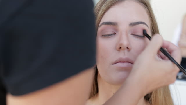 woman having eye shadow applied - stage make up stock videos and b-roll footage