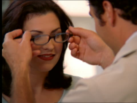 vidéos et rushes de woman having eyeglasses placed on face by doctor / nodding + smiling - opticien