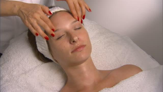 cu, zi, woman having face massage - タオルにくるまる点の映像素材/bロール