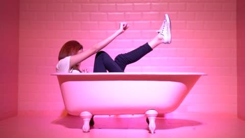 kvinna att ha roligt och dansa i den rosa bathtube - helgaktivitet bildbanksvideor och videomaterial från bakom kulisserna