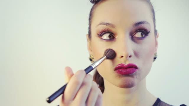 Woman having fun applying makeup