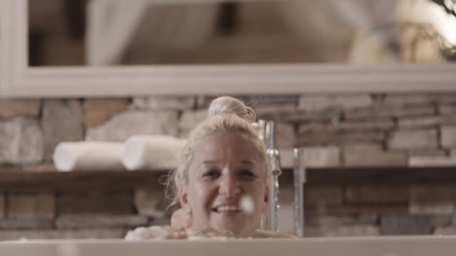 slo mo woman having fun blowing soap foam while taking a bubble bath - soap sud video stock e b–roll