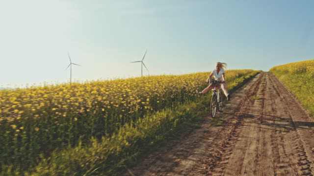 slo mo woman having fun cycling along canola fields with wind turbines in the distance - turbine stock videos & royalty-free footage