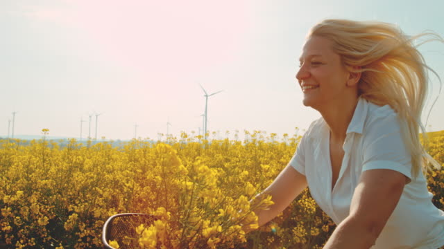 super slo mo - time warp effect woman having fun cycling along canola fields with wind turbines in the distance - mid adult women stock videos & royalty-free footage