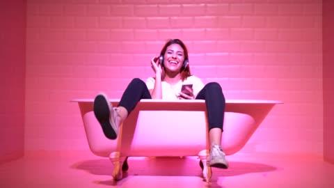 vídeos y material grabado en eventos de stock de mujer tener diversión en la bañera rosa - diseño temas