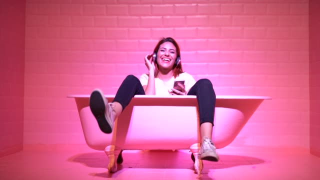 stockvideo's en b-roll-footage met vrouw having fun in de roze bad - hoofdtelefoon