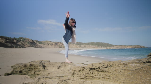 A woman having fun in the rocks, at Mornington Peninsula, Victoria, Australia