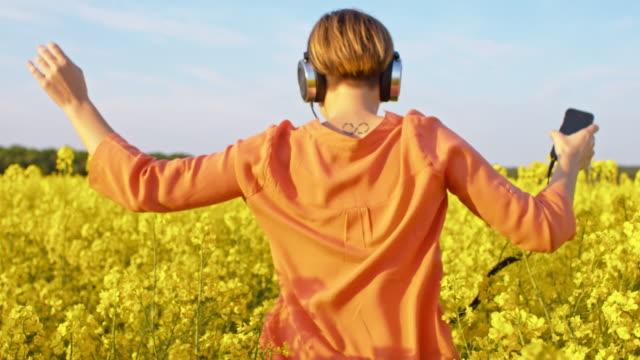 SLO MO mulher se divertindo ouvindo música na natureza